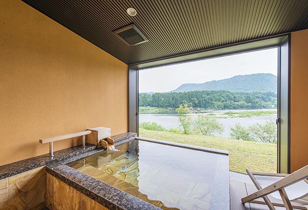 露天風呂付き客室「せせらぎ」の格調漂う天然石の露天風呂と阿賀野川の眺望。贅沢な空間です。
