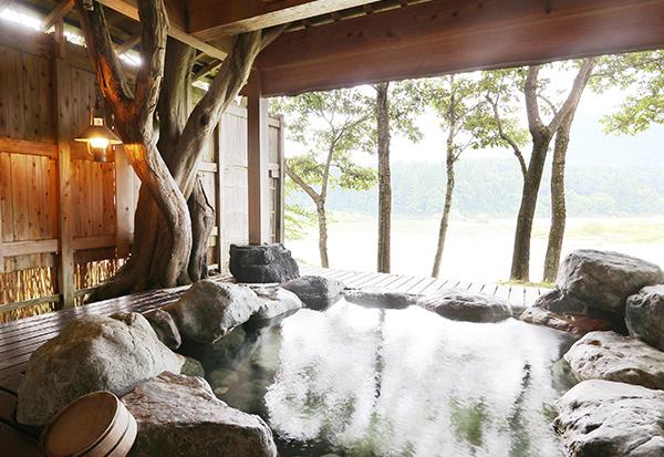 貸切露天風呂からの阿賀野川の眺望、豪快な岩風呂と檜造りの屋根