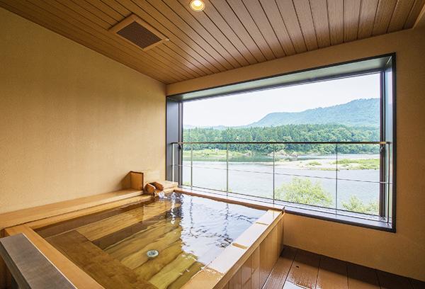 露天風呂付き客室「そよかぜ」のひばの香り漂う露天風呂お阿賀野川の眺望。心落ち着く空間です。