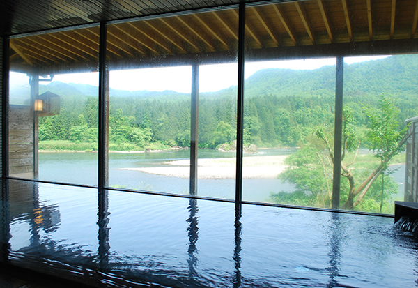 大浴場からの阿賀野川の眺望、全面ガラスのフレームに広がる大パノラマ