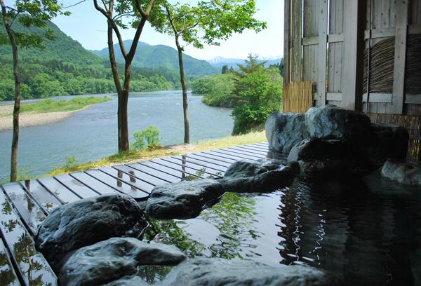 野趣あふれる岩造りの露天風呂。地元谷沢の豪快な石を使用し、もみじの大木を貫通させた屋根は檜造りです。