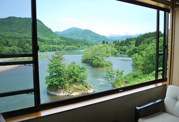 部屋からの阿賀野川の眺望。河鵜や青鷺が優雅に飛ぶ姿を眺められます。また、遠く対岸にはSL列車や夜行電車がみえることも。
